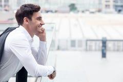 Ο όμορφος νέος επιχειρηματίας χρησιμοποιεί το τηλέφωνο για Στοκ Φωτογραφία