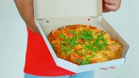 Ο όμορφος νέος εργαζόμενος παράδοσης κόκκινο σε ομοιόμορφο κρατά μια πίτσα, εξετάζει τη κάμερα και χαμογελά, στο γκρίζο υπόβαθρο φιλμ μικρού μήκους