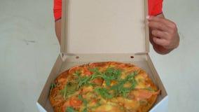 Ο όμορφος νέος εργαζόμενος παράδοσης κόκκινο σε ομοιόμορφο κρατά μια πίτσα, εξετάζει τη κάμερα και χαμογελά, στο γκρίζο υπόβαθρο απόθεμα βίντεο
