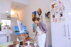 Ο όμορφος νέος ζωγράφος χρωματίζει τις βούρτσες και το πετρέλαιο χρήσεων εικόνων, και Στοκ εικόνα με δικαίωμα ελεύθερης χρήσης