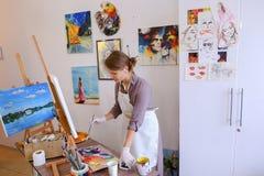 Ο όμορφος νέος ζωγράφος χρωματίζει τις βούρτσες και το πετρέλαιο χρήσεων εικόνων, και Στοκ εικόνες με δικαίωμα ελεύθερης χρήσης
