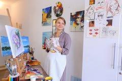 Ο όμορφος νέος ζωγράφος χρωματίζει τις βούρτσες και το πετρέλαιο χρήσεων εικόνων, και Στοκ Φωτογραφίες