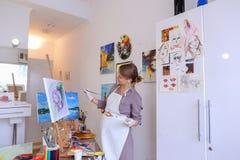 Ο όμορφος νέος ζωγράφος χρωματίζει τις βούρτσες και το πετρέλαιο χρήσεων εικόνων, και Στοκ Εικόνα