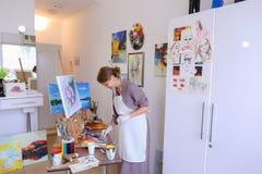 Ο όμορφος νέος ζωγράφος χρωματίζει τις βούρτσες και το πετρέλαιο χρήσεων εικόνων, και Στοκ φωτογραφία με δικαίωμα ελεύθερης χρήσης