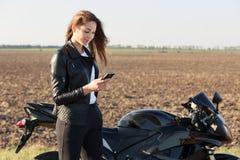 Ο όμορφος νέος θηλυκός ποδηλάτης φορά το κόκκινο μοντέρνο bandana και τα μαύρα ενδύματα, κρατώντας το κινητό τηλέφωνο στα χέρια,  στοκ εικόνα