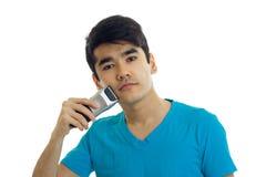 Ο όμορφος νέος τύπος σε μια μπλούζα ξυρίζει τη χρησιμοποίηση μηχανών ξυρίσματος Στοκ Φωτογραφίες