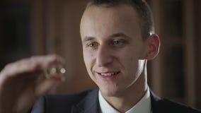 Ο όμορφος νεαρός άνδρας αγοριών που παρουσιάζει έναν γάμο χτυπά και που χαμογελά στο σπίτι απόθεμα βίντεο