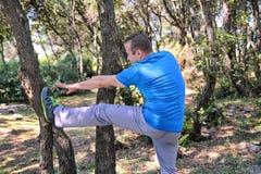 Ο όμορφος νεαρός άνδρας κάνει τις τεντώνοντας ασκήσεις στο δασικό αθλητικό τύπο που φορά sportswear στη φύση τοπίων υπαίθρια Στοκ φωτογραφίες με δικαίωμα ελεύθερης χρήσης