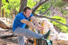 Ο όμορφος νεαρός άνδρας κάνει τις τεντώνοντας ασκήσεις στο δασικό αθλητικό τύπο που φορά sportswear στη φύση τοπίων υπαίθρια Στοκ Εικόνα