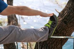 Ο όμορφος νεαρός άνδρας κάνει τις τεντώνοντας ασκήσεις στο δασικό αθλητικό τύπο που φορά sportswear στη φύση τοπίων υπαίθρια Στοκ Φωτογραφία