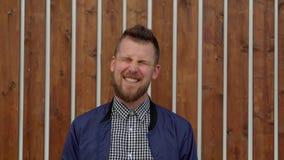 Ο όμορφος νεαρός άνδρας μορφάζει και γελά κοντά στον ξύλινο τοίχο υπαίθριο, απόθεμα βίντεο