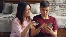 Ο όμορφος νεαρός άνδρας πληρώνει για τις αγορές Διαδικτύου χρησιμοποιώντας το smartphone ενώ η ελκυστική σύζυγός του κάθεται εκτό απόθεμα βίντεο