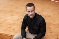 Ο όμορφος νεαρός άνδρας σε ένα καθιερώνον τη μόδα μαύρο σακάκι άνοιξη στο μοντέρνο μπεζ παντελόνι με ένα hairstyle χαλαρώνει τη σ στοκ εικόνες