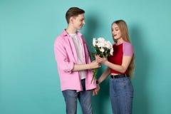 Ο όμορφος νεαρός άνδρας στο ρόδινο πουκάμισο δίνει μια ανθοδέσμη των άσπρων λουλουδιών στην όμορφη ξανθή φίλη του στοκ εικόνες