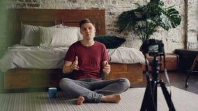 Ο όμορφος νεαρός άνδρας blogger καταγράφει το βίντεο για τους συνδρομητές του που μιλούν και που χρησιμοποιώντας την επαγγελματικ απόθεμα βίντεο