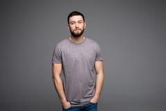 Ο όμορφος νεαρός άνδρας, αγόρι, που θέτει στο γκρίζα πουκάμισο και τα τζιν με παραδίδει τις τσέπες στο γκρι Στοκ εικόνες με δικαίωμα ελεύθερης χρήσης