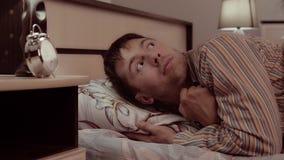 Ο όμορφος νεαρός άνδρας που βρίσκεται στο κρεβάτι και που χαμογελά ανοίγει τα μάτια του ευρέως και τις δορές κάτω από ένα κάλυμμα απόθεμα βίντεο