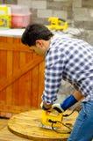 Ο όμορφος νεαρός άνδρας που φορά την εργασία φορά γάντια στο λειτουργώντας ξύλο με το ηλεκτρικό τορνευτικό πριόνι Στοκ φωτογραφία με δικαίωμα ελεύθερης χρήσης
