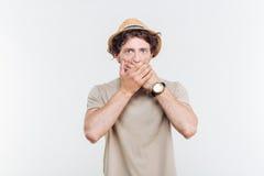 Ο όμορφος νεαρός άνδρας στο καπέλο καλύπτει το στόμα του με το χέρι Στοκ Φωτογραφίες