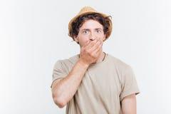 Ο όμορφος νεαρός άνδρας στο καπέλο καλύπτει το στόμα του με το χέρι Στοκ Εικόνες