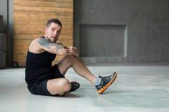 Ο όμορφος νεαρός άνδρας χαλαρώνει στη γυμναστική μετά από να εκπαιδεύσει στοκ φωτογραφία με δικαίωμα ελεύθερης χρήσης