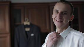Ο όμορφος νεόνυμφος καθορίζει το πουκάμισό του Γαμήλιο πρωί o o απόθεμα βίντεο