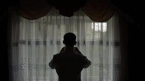 Ο όμορφος νεόνυμφος καθορίζει το πουκάμισό του Γαμήλιο πρωί Σκιαγραφία o απόθεμα βίντεο