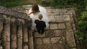 Ο όμορφος νεόνυμφος προέρχεται από πίσω στην όμορφη νύφη του, αγκαλιάζει το της και το φιλί μεριδίου στα σκαλοπάτια του παλαιού κ απόθεμα βίντεο