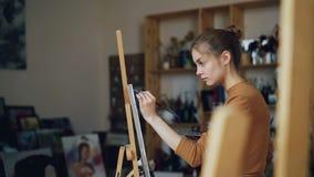 Ο όμορφος ξανθός ζωγράφος χρωματίζει την εικόνα σε μόνη χρησιμοποίηση στούντιο τέχνης paintrush και την παλέτα με τα χρώματα Η νέ φιλμ μικρού μήκους