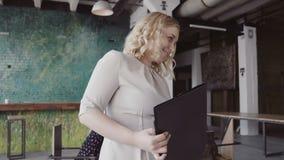 Ο όμορφος ξανθός θηλυκός περίπατος αρχηγών ομάδας μέσω του γραφείου, ελέγχει την εργασία του υπαλλήλου, δίνει την κατεύθυνση στο  απόθεμα βίντεο