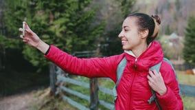 Ο όμορφος οδοιπόρος γυναικών στο κόκκινο σακάκι με το μικρό σακίδιο πλάτης στέκεται στο υπόβαθρο ξύλων χρησιμοποιώντας το τηλέφων απόθεμα βίντεο