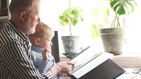 Ο όμορφος παππούς παρουσιάζει στον εγγονό του οικογενειακό λεύκωμά του Οικογενειακή αξία απόθεμα βίντεο
