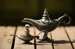 Ο όμορφος παλαιός λαμπτήρας μετάλλων στο αληθινό ύφος Aladin, μικρότερο πρότυπο τοποθέτησε δίπλα σε το, που κάθεται στην ξύλινη ε Στοκ Εικόνες