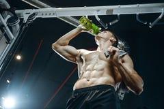 Ο όμορφος πρότυπος νεαρός άνδρας παίρνει την αθλητική διατροφή Στοκ εικόνα με δικαίωμα ελεύθερης χρήσης
