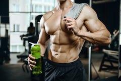 Ο όμορφος πρότυπος νεαρός άνδρας παίρνει την αθλητική διατροφή Στοκ Φωτογραφία