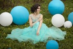 Ο όμορφος πτυχιούχος κοριτσιών σε ένα μπλε φόρεμα κάθεται στη χλόη κοντά τα μεγάλα μπλε και άσπρα μπαλόνια Εύθυμος κομψός Στοκ εικόνες με δικαίωμα ελεύθερης χρήσης