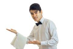 Ο όμορφος σερβιτόρος σε ένα άσπρο πουκάμισο και με μια πεταλούδα στο λαιμό του παρουσιάζει το χέρι μπροστινό και που χαμογελά Στοκ Εικόνες
