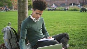 Ο όμορφος σοβαρός σπουδαστής afro εργάζεται στο πάρκο κοντά στο πανεπιστήμιο απόθεμα βίντεο