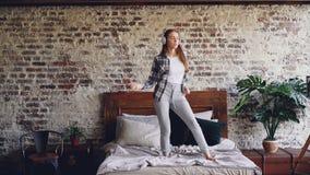 Ο όμορφος σπουδαστής στα περιστασιακά ενδύματα χορεύει στο κρεβάτι και το άκουσμα τραγουδιού στη μουσική με τα ασύρματα ακουστικά φιλμ μικρού μήκους