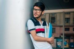 Ο όμορφος σπουδαστής με τα βιβλία στα χέρια φορά τα γυαλιά και κοιτάζει κατά μέρος Στοκ φωτογραφίες με δικαίωμα ελεύθερης χρήσης