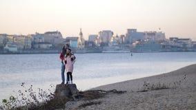 Ο όμορφος τύπος αγκαλιάζει ένα νέο κορίτσι στην παραλία Το ζευγάρι κοιτάζει προς τα εμπρός Χαμόγελο Φθινόπωρο 4K η αργή Mo φιλμ μικρού μήκους