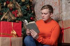 Ο όμορφος τύπος διαβάζει μια συνεδρίαση βιβλίων κάτω από το δέντρο που περιβάλλεται από τα κιβώτια των δώρων Χριστούγεννα και δώρ στοκ εικόνες με δικαίωμα ελεύθερης χρήσης