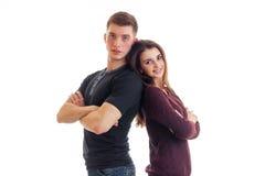 Ο όμορφος τύπος και ένα νέο γοητευτικό κορίτσι που χαμογελά και που στέκεται το ένα πίσω στο άλλο δίνουν Στοκ Εικόνες