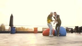 Ο όμορφος τύπος κρατά τη φίλη από το χέρι και τα τρεξίματα στις πολύχρωμες πολυθρόνες στο πεζούλι του καφέ styl υπαίθρια απόθεμα βίντεο