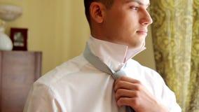 Ο όμορφος τύπος ντύνει έναν δεσμό και χαμογελά ευτυχής εκλεκτής ποιότητας γάμος ημέρας ζευγών ιματισμού Ο νεόνυμφος φορά έναν δεσ απόθεμα βίντεο