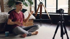 Ο όμορφος τύπος στον περιστασιακό ιματισμό blogger καταγράφει το βίντεο για το Διαδίκτυό του vlog στο σπίτι με την επαγγελματική  απόθεμα βίντεο