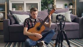 Ο όμορφος τύπος vlogger καταγράφει το βίντεο για τους συνδρομητές που διδάσκουν για να παιχτεί η κιθάρα κρατώντας το μουσικό όργα απόθεμα βίντεο