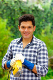 Ο όμορφος χαμογελώντας νεαρός άνδρας που φορά την εργασία φορά γάντια στο λειτουργώντας ξύλο με το ηλεκτρικό τορνευτικό πριόνι Στοκ εικόνες με δικαίωμα ελεύθερης χρήσης