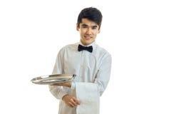 Ο όμορφος χαμογελώντας σερβιτόρος με τη μαύρη τρίχα σε ένα άσπρο πουκάμισο και με μια πεταλούδα κρατά σε διαθεσιμότητα την πετσέτ Στοκ εικόνες με δικαίωμα ελεύθερης χρήσης