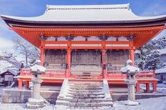 Ο όμορφος χειμώνας εποχιακός της κόκκινης παγόδας στο ναό kiyomizu-Dera που περιβλήθηκε με τα δέντρα κάλυψε το άσπρο υπόβαθρο χιο Στοκ εικόνες με δικαίωμα ελεύθερης χρήσης
